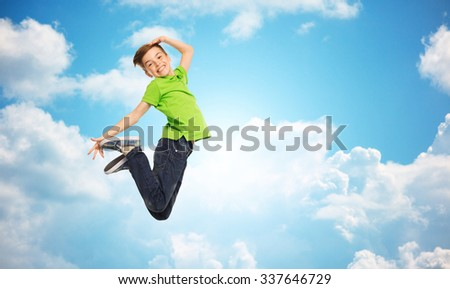 happiness, childhood, freedom, movement and people concept - smiling boy jumping in air over blue sky and clouds background