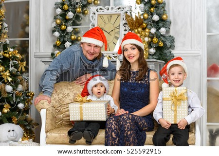 happiness christmas family concept - smiling family in santa helper hats with many gift boxes