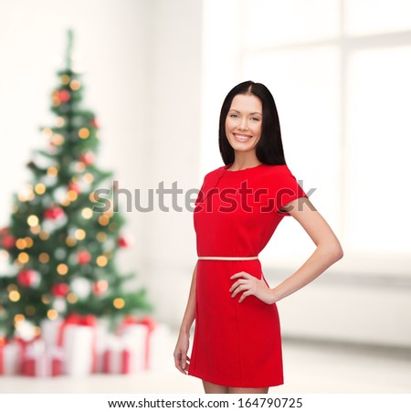 happiness, christmas, xmas and people concept - smiling young woman in red dress - stock photo