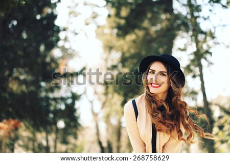 Happiness, consumerism, fashion and people concept - smiling young trendy hipster girl on city background in the sunlight outdoor - stock photo