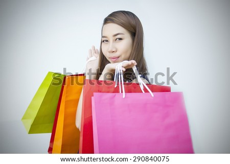 happiness, consumerism, sale and people concept - smiling young woman asian with shopping bags over mall/supermarket background