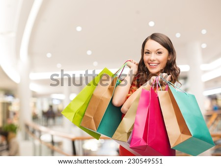 happiness, consumerism, sale and people concept - smiling young woman with shopping bags over mall background - stock photo