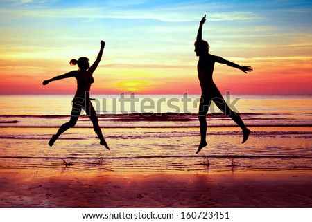 happiness, couple jumping on the beach - stock photo