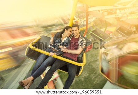 Happiness couple riding on ferris wheel at amusement park - stock photo