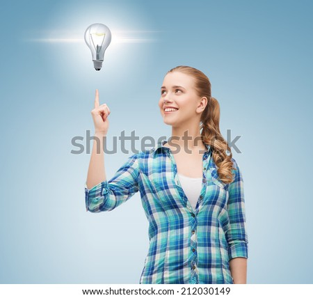 happiness, electricity, idea and people concept - smiling young woman pointing finger up to electric bulb over blue background