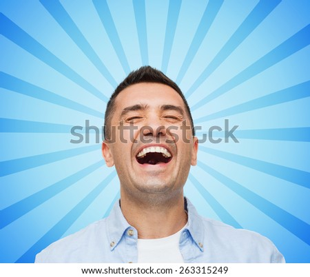happiness, emotions and people concept - face of laughing man blue burst rays background - stock photo