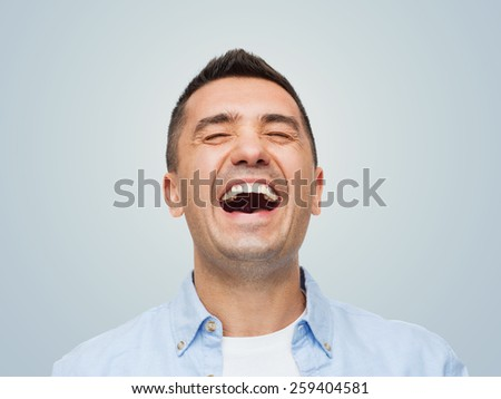 happiness, emotions and people concept - laughing man over gray background - stock photo