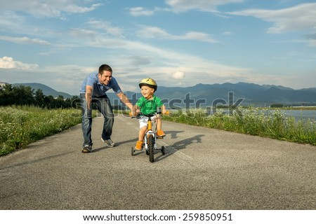 Happiness Father and son on the bicycle outdoor - stock photo