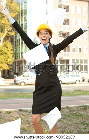happiness female engineer celebrating her success, throwing paper in the air - stock photo