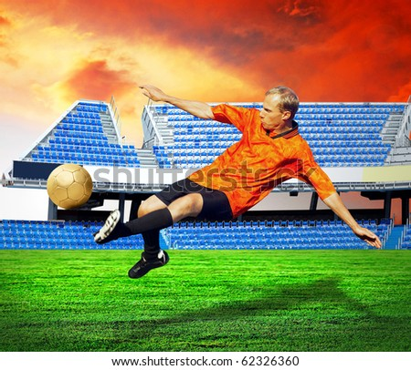 Happiness football player after goal on the field of stadium under sky - stock photo