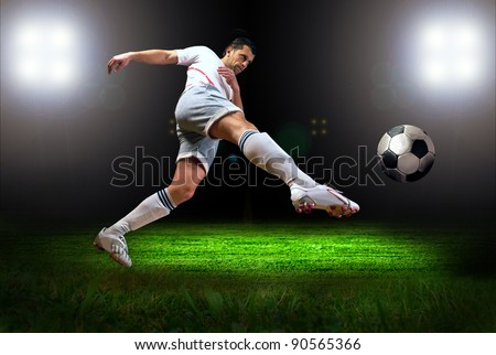 Happiness football player after goal on the field of stadium with light - stock photo