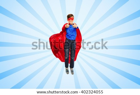 happiness, freedom, childhood, movement and people concept - boy in red super hero cape and mask flying in air and showing thumbs up over blue burst rays background - stock photo
