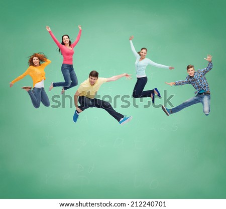 happiness, freedom, friendship, education and people concept - group of smiling teenagers jumping in air over green board background - stock photo