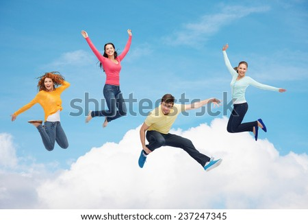 happiness, freedom, friendship, movement and people concept - group of smiling teenagers jumping in air over blue sky with white cloud background - stock photo