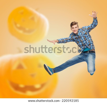 happiness, freedom, holidays and people concept - smiling young man jumping in air over halloween pumpkins background
