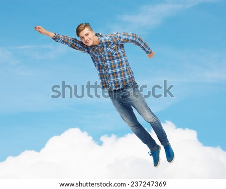 happiness, freedom, movement and people concept - smiling young man flying in air over blue sky with white cloud background - stock photo