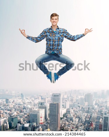 happiness, freedom, movement and people concept - smiling young man hanging of flying in air in pose of yoga over city background - stock photo