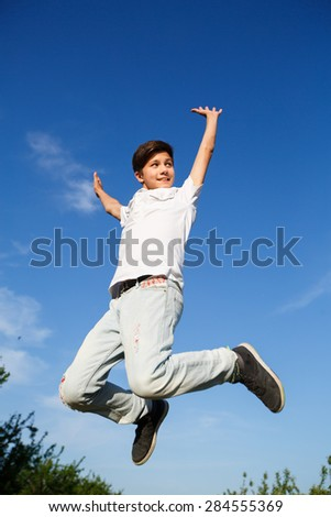 happiness, freedom, movement and people concept - smiling young man jumping - stock photo