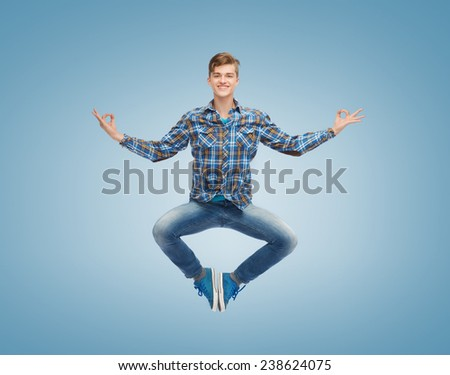 happiness, freedom, movement and people concept - smiling young man jumping in air over blue background - stock photo