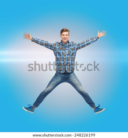 happiness, freedom, movement and people concept - smiling young man jumping in air over blue laser background - stock photo