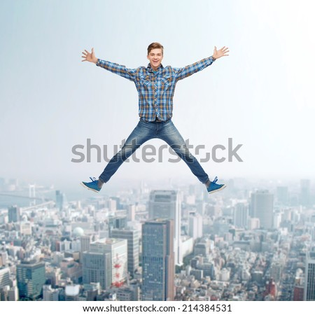 happiness, freedom, movement and people concept - smiling young man jumping in air over city background - stock photo