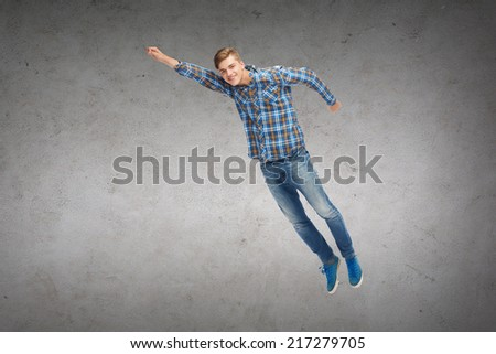 happiness, freedom, movement and people concept - smiling young man jumping in air over concrete wall background - stock photo
