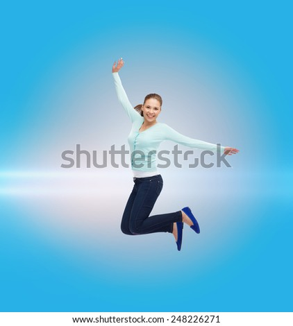 happiness, freedom, movement and people concept - smiling young woman jumping in air over blue laser background