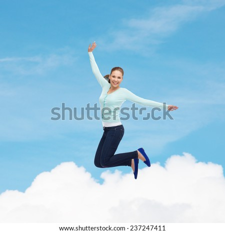 happiness, freedom, movement and people concept - smiling young woman jumping in air over blue sky with white cloud background