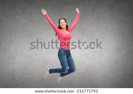 happiness, freedom, movement and people concept - smiling young woman jumping in air over concrete wall background - stock photo