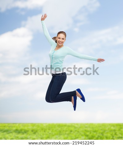 happiness, freedom, movement, summer and people concept - smiling young woman jumping in air over natural background - stock photo