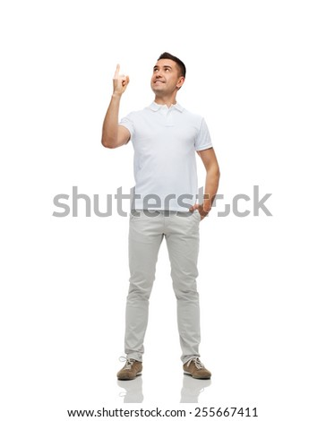 happiness, gesture and people concept - smiling man pointing finger up - stock photo