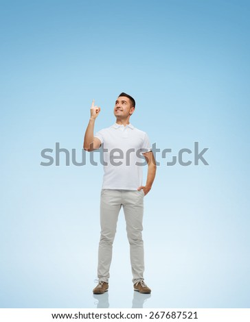 happiness, gesture and people concept - smiling man pointing finger up over blue background - stock photo