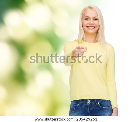 happiness, gesture and people concept - smiling woman pointing finger at you - stock photo