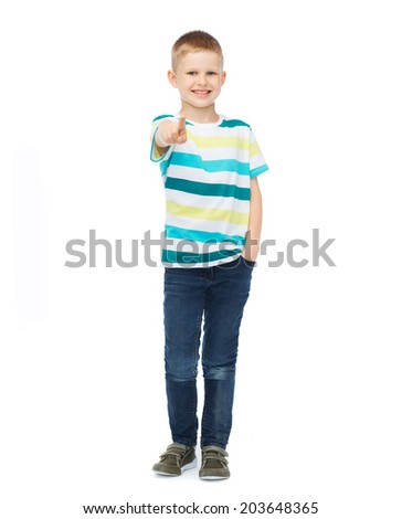 happiness, gesture, childhood and people concept - smiling little boy in casual clothes pointing his finger at you - stock photo