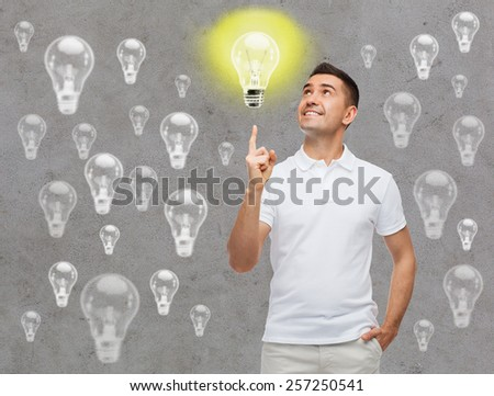 happiness, gesture, idea, inspiration and people concept - smiling man pointing finger up lighting bulb over gray background - stock photo