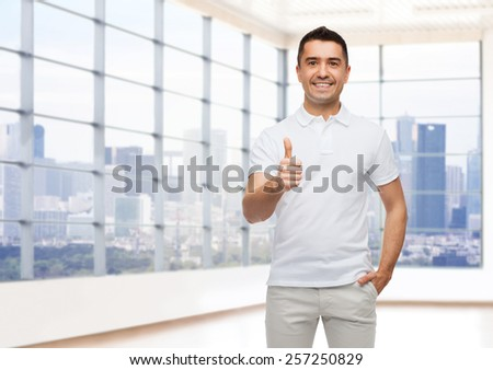 happiness, gesture, real estate and people concept - smiling man showing thumbs up over empty apartment or office room with big window and city view background - stock photo