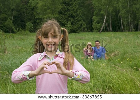 Happiness girl shows heart. Mother and father are sitting on the grass in the park.  Young pretty girl make gesture heart.  Happy family. - stock photo