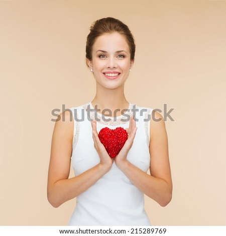 happiness, health, charity and love concept - smiling woman in white dress with red heart over beige background - stock photo