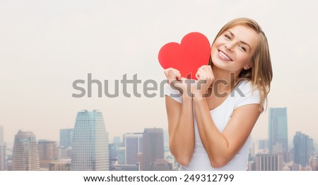 happiness, health, people, holidays and love concept - smiling young woman in white t-shirt holding red heart over city background - stock photo