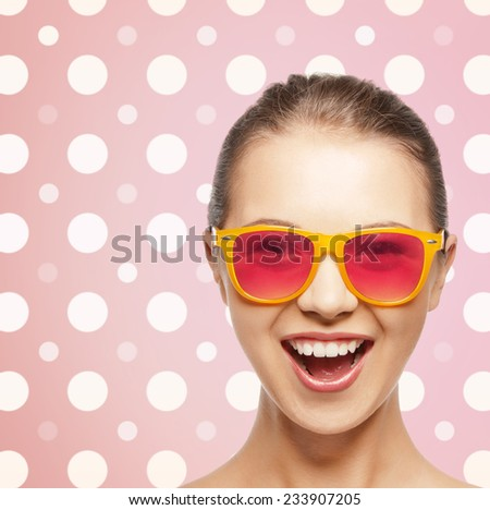 happiness, holidays, fashion and people concept - happy laughing teenage girl in shades over pink and white polka dots pattern background - stock photo