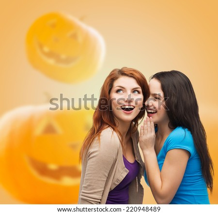 happiness, holidays, firendship and people concept - smiling teenage girls gossiping over halloween pumpkins background - stock photo