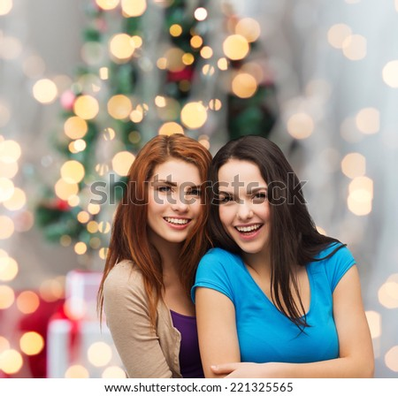 happiness, holidays, friendship and people concept - smiling teenage girls hugging over christmas tree background - stock photo