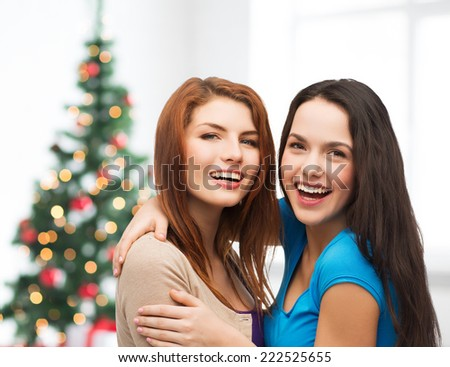 happiness, holidays, friendship and people concept - smiling teenage girls hugging over living room and christmas tree background - stock photo