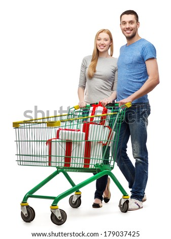 happiness, holidays, shopping and couple concept - smiling couple with shopping cart and gift boxes in it