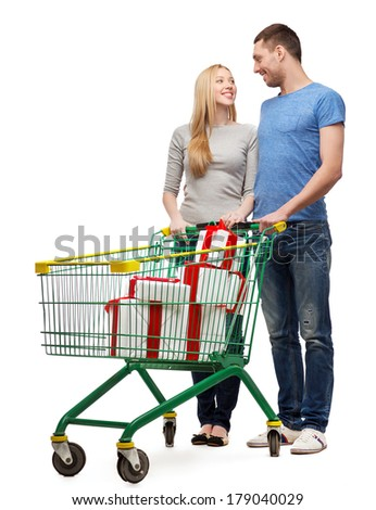 happiness, holidays, shopping and couple concept - smiling couple with shopping cart and gift boxes in it looking at each other