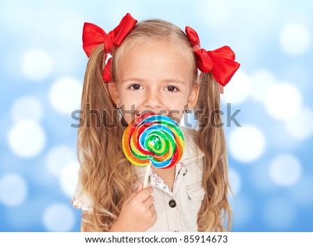 Happiness in the eyes of a child with lollipop - stock photo