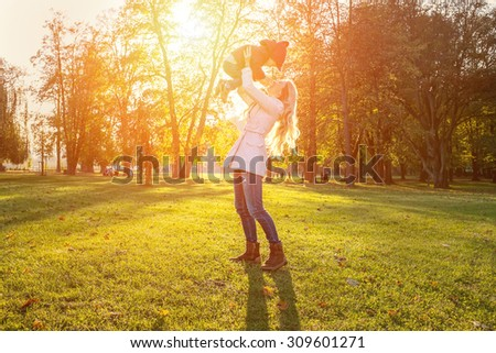 Happiness mother and son in autumn - stock photo