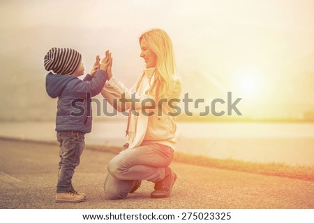 Happiness mother and son under sun light - stock photo