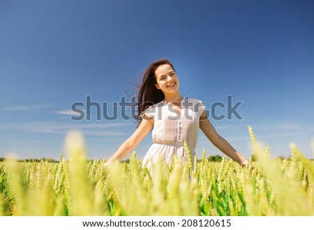 happiness, nature, summer, vacation and people concept - smiling young woman on cereal field - stock photo