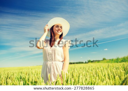 happiness, nature, summer, vacation and people concept - smiling young woman wearing straw hat on cereal field - stock photo